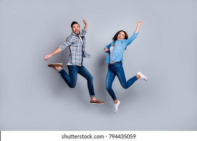 He vs She full length portrait of attractive, playful, cheerful, comic couple in casual outfit, jeans, shirts jumping  over grey background