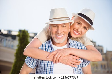 He vs she together forever! Portrait of cheerful positive grandma and granddad in straw hats, attractive man carrying on back charming woman, enjoying time together outdoor