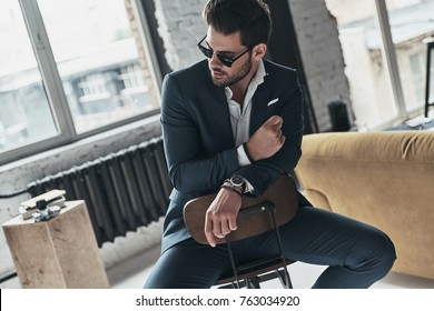 He will melt your heart. Handsome young man in full suit and eyewear looking away while sitting on the stool