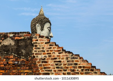 Head of the Buddha and old brick wall