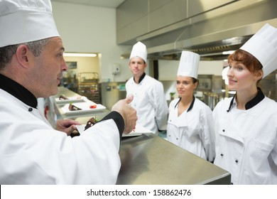 Head chef rating the plate of one of his apprentices in a kitchen