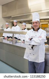 Head chef standing with arms crossed and team standing behind him