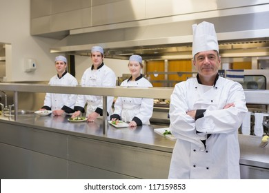 Head chef standing smiling with team behind him in the kitchen
