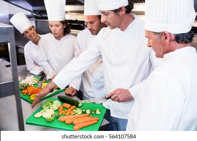 Head chef teaching his colleagues how to slice vegetables in the kitchen