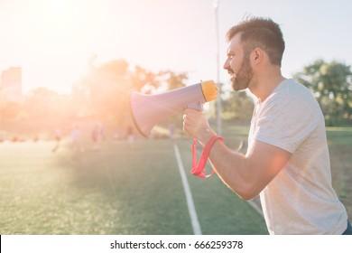 The head coach screams into the megaphone. Football game. Concept