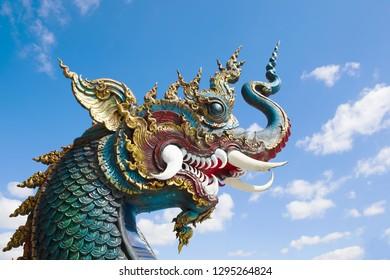 The head of a dragon against a blue sky. Buddhist temple Wat Rong Seur Ten (Blue Temple). Chiang Rai, Thailand