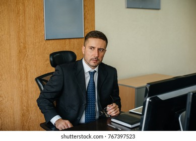 The head of the enterprise sits in his office at the computer. Business, finance.