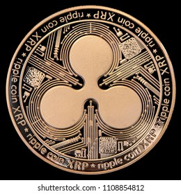 Head face of a physical golden coin representing a Ripple (XRP) isolated on black background. This crypto currency is the third by market volume