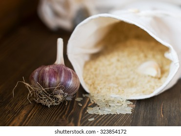 head of garlic and a bag of rice on wooden background