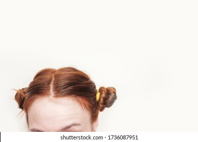 Head of a girl with two messy twisted curled red hair buns on white background. Creative hairstyle. Copyspace.