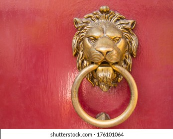 head gold lion knocks on the red door