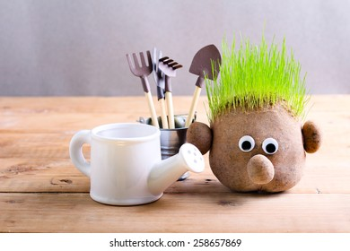 Head with grass and gardening tools on wooden table