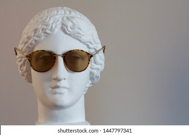 the head of the Greek goddess Muse wearing sunglasses