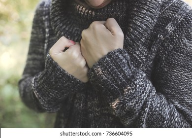 head and hands, beautiful brunette woman with sweater with clenched fists, concept pain, depression and loneliness, dark style and toning