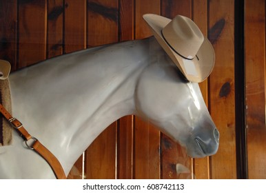 Head of a lifesize plastic horse model wearing a cowboy hat as store window display