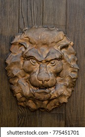 A head of the lion engraved on the gate door. Covered with varnish. With golden orange shine.