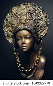 Head of mannequin in decorated bronze kokoshnick, dark studio background