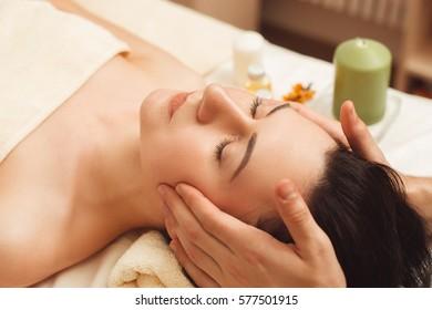 Head massage at beauty salon closeup. Portrait of young brunette enjoying relaxing beating. Pleasure, rest, body care, health , resort concept