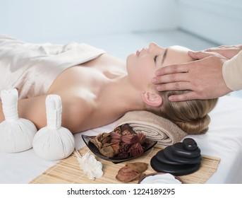 Head massage. Masseur doing massage the head of woman in a spa salon.