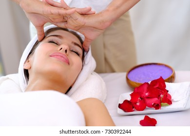 Head massage at spa. Attractive Happy relaxing girl at beauty spa treatment. Beauty young woman recieving head massage at spa, massager's hands on the woman's head spa concept.