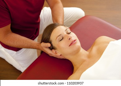 head and neck massage of a beautiful woman. a woman receives a head and neck pressure point massage by her chiropractor