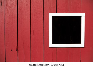 Head on close up of exterior wall of classic red barn in bright sunlight with black square window outlined by white windowsill frame in rural geometric agriculture farm background