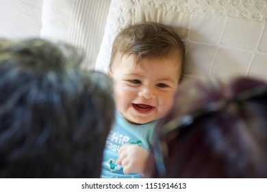 head portrait of baby boy  laying down smiling to grandparents