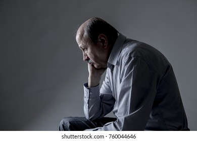 head portrait of senior mature old man on his 60s looking sad and worried suffering pain and depression in sadness face expression isolated on grey background in retirement and aging frustration