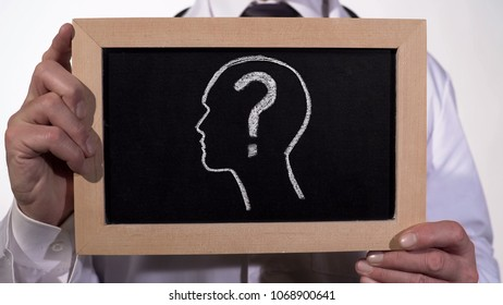 Head with questionmark drawn on blackboard in physician hands, diagnostics, stock footage