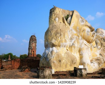 Head of the Reclining Buddha at Wat Lokaya Sutha, Ayuthaya, Thailand with the ruined Prang in the background