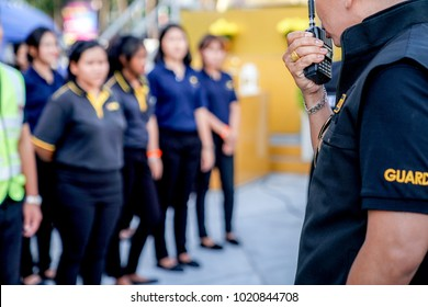 head of security guard call meeting and talk into walkie talkie for communication to the team.