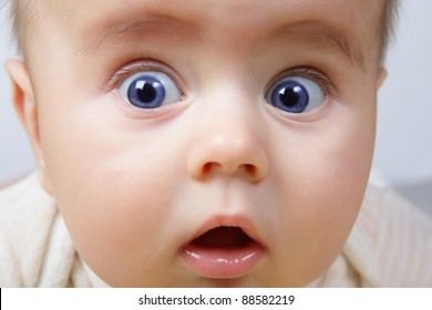 head shoot of cute baby with blue eyes and surprise look