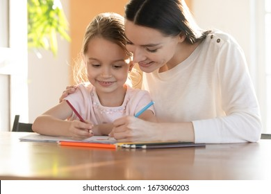 Head shot affectionate young mommy embracing shoulders of happy small daughter, drawing pictures together at home. Smiling millennial babysitter nanny cuddling little kid girl, painting in album.