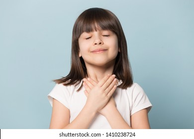 Head shot appreciative little brown-haired girl closed eyes holding hands on chest symbol of deep grateful feelings isolated on blue background, adopted child new parents, Gratitude Day concept image
