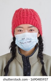 head shot of Asian woman with my mask protects you written in marker on her face mask