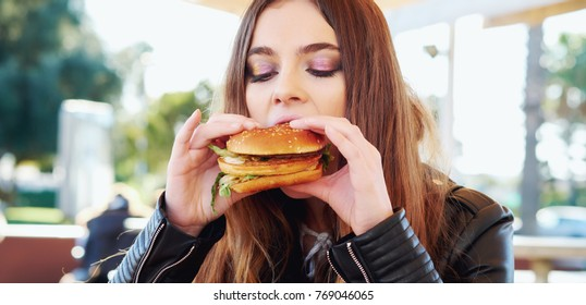 Head shot of attractive brunette teenager girl eating a hamburger, generation Z Portrait of young woman with burger, holding in hands. Unhealthy eating, fast fat food, overweight concept