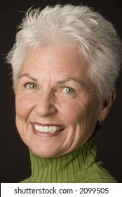 Head shot of a beautiful 55 to 60 year old woman against a black background.