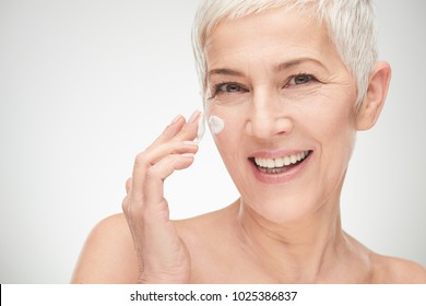 Head shot of beautiful senior woman putting on the creme.