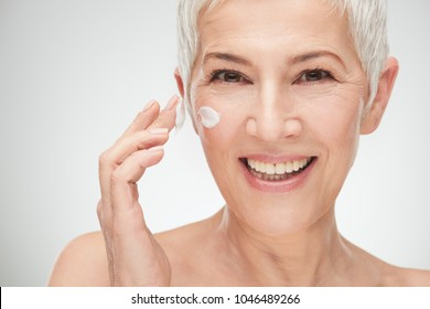 Head shot of beautiful senior woman putting on the cream.