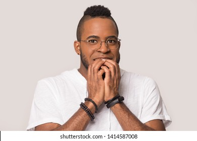 Head shot black guy in glasses feeling fear pose isolated on grey background, african nervous coward man nibbles nails, frightened person, stressful situations, lack of self-confidence, phobia concept
