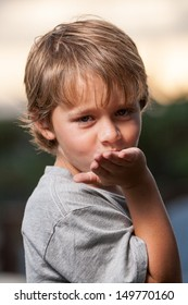 Head shot of a blond hair little boy blowing a kiss to the camera with a beautiful sunset in the background
