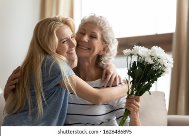 Head shot cheerful grown up daughter cuddling senior old mother, telling congratulations with birthday or special occasion, presenting field flowers. Grateful elderly woman embracing granddaughter.