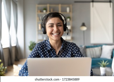 Head shot cheerful smiling pretty hindu ethnic girl sitting at table with computer, wearing headphones with mic, looking at camera. Happy indian woman professional tutor educating client online.