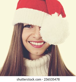Head shot of Christmas teenage girl with freckles. Closeup studio portrait of cute young woman with long brown hair and knitted Santa Claus hat. Square format, instagram filter.
