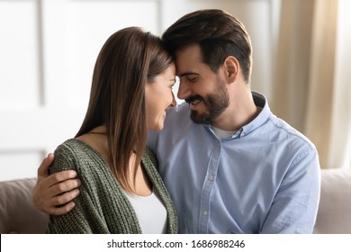 Head shot close up affectionate young man cuddling attractive smiling woman wife, touching foreheads. Happy loving family couple enjoying sweet tender moment, showing love care devotion at home.
