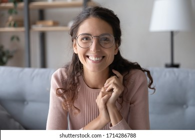 Head shot close up beautiful smiling young woman in eyewear looking at camera, holding video job interview from home. Web cam view happy smart female blogger recording vlog alone in living room.