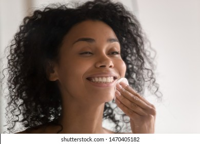 Head shot close up happy african american young woman standing with wide smile, using disposable cotton pads, removing make up before sleeping or cleaning face, applying lotion toner on clean skin.