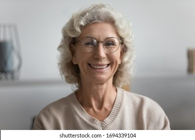 Head shot close up happy elderly senior woman in eyeglasses posing for photo. Portrait of smiling middle aged grandmother in eyewear looking at camera, holding video call with relatives or friends.