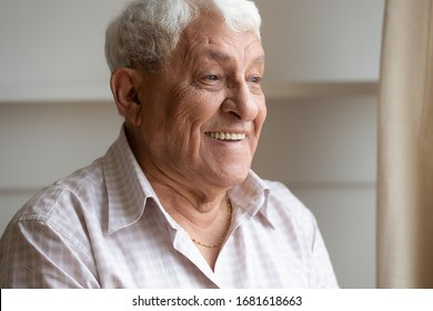 Head shot close up happy older man with healthy smile dreaming about future, good pleasant memories, looking to away in window, dreamy positive mature male, serene peaceful elderly grandfather