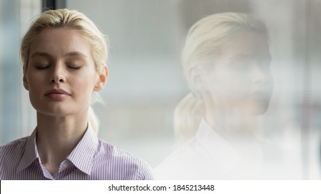 Head shot close up mindful young businesswoman breathing fresh air with closed eyes near window, enjoying calm break pause time in office, reducing stress pressure during workday, copy space for text.